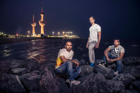 Three Athletes pausing in front of Kuwait Towers